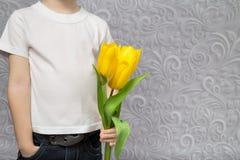 Junge mit einem Blumenstrauß von gelben Tulpen Lizenzfreie Stockbilder