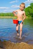 Junge mit einem Eimer Wasser Stockbild