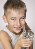 Junge mit einem Glas Wasser Stockbild