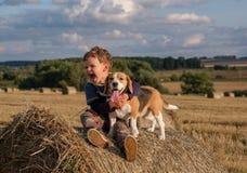 Junge mit einem Hundspürhund auf einem Heuschober Stockbild