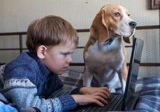 Junge mit einem Laptop und einem Spürhund Lizenzfreies Stockfoto