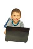 Junge mit einem Laptoplügen Stockfotos