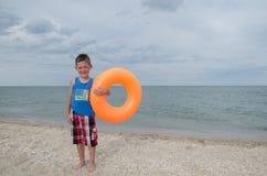 Junge mit einem Schwimmenkreis steht auf dem Ufer des Meeres Lizenzfreies Stockbild