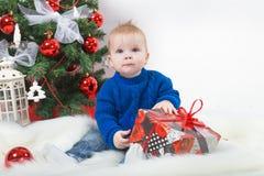 Junge mit einem Weihnachtsgeschenk am Weihnachtsbaum Lizenzfreie Stockfotos