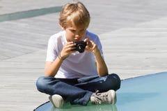 Junge mit einer Digitalkamera, die draußen Fotos macht Lizenzfreies Stockbild