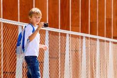 Junge mit einer Digitalkamera, die Fotos in der Straße macht Stockbild