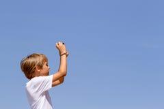 Junge mit einer Digitalkamera gegen blauen Himmel Stockfotografie