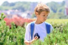 Junge mit einer Digitalkamera, welche die Fotos im Freien macht Stockbilder