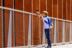 Junge mit einer Digitalkamera, welche die Fotos im Freien macht Lizenzfreies Stockbild