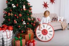 Junge mit einer großen Uhr im Weihnachtsbaum Lizenzfreie Stockfotos
