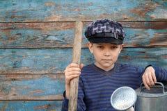 Junge mit einer Schaufel und einer Gießkanne sitzt nahe hölzerner Wand Stockfotografie