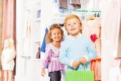 Junge mit Einkaufstasche und lachendem Mädchen hinter ihm Lizenzfreie Stockfotos