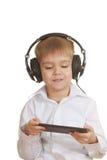 Junge mit elektronischer Auflage und Telefonen Stockbilder