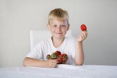 Junge mit Erdbeeren Stockfoto