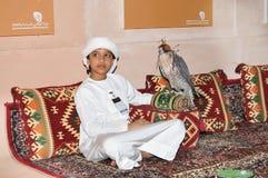 Junge mit Falken in Abu Dhabi International Hunting und in der Reiterausstellung (ADIHEX) Lizenzfreie Stockbilder