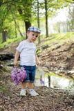 Junge mit Flieder und Vogelkäfig auf einem Teich Stockfoto