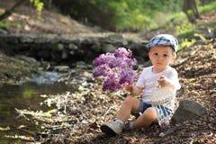Junge mit Flieder und Vogelkäfig auf einem Teich Stockfotografie