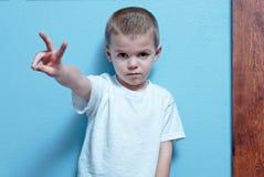 Junge mit Friedenszeichen Stockfoto