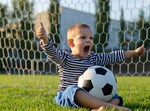 Junge mit Fußball schreiend mit Freuden Lizenzfreie Stockfotografie