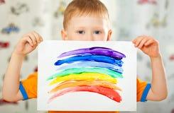 Junge mit gemaltem Regenbogen auf Papier Stockbild