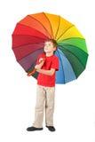 Junge mit großem mehrfarbigem Regenschirm auf Weiß Lizenzfreie Stockfotos