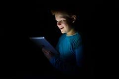 Junge mit hellem Haarspiel mit einer Tablette in der Dunkelheit Stockfotos