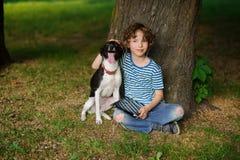 Junge mit Hund sitzt auf der Erde unter einem Baum Stockfoto