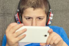 Junge mit Kopfhörern und Handy in der Hand Lizenzfreie Stockfotografie
