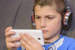 Junge mit Kopfhörern und Handy in der Hand Stockbilder