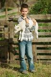 Junge mit Lamm auf dem Bauernhof Stockfotos
