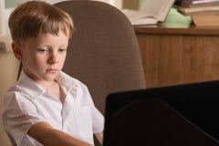 Junge mit Laptop bei Tisch Lizenzfreie Stockbilder