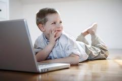 Junge mit Laptop-Computer niederlegend auf dem Fußboden Lizenzfreies Stockbild