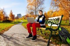 Junge mit Laptop draußen Lizenzfreies Stockfoto