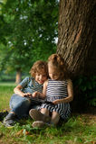 Junge mit Mädchen von 7-8 Jahren sitzen auf der Erde unter einem Baum und Spiel an der Tablette Stockfotografie