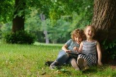 Junge mit Mädchen von 7-8 Jahren sitzen unter einem anschmiegenden Baum und Spiel auf der Tablette Lizenzfreies Stockfoto