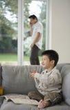 Junge mit Malbuch während Vater-On Call At-Haus Stockfotografie