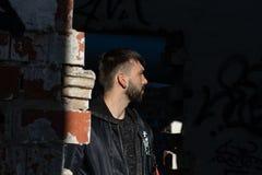 Junge mit moderner Frisur und Bart, im Profil in einem verlassenen Platz lizenzfreies stockbild