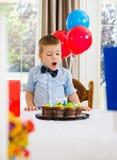 Junge mit Mund-offenem schauendem Kuchen lizenzfreie stockbilder