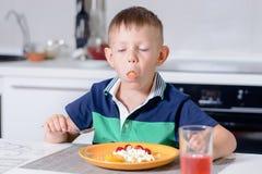 Junge mit Mund-vollem Essenkäse und Frucht Stockbilder