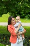Junge mit Mutter im Park Stockfotos