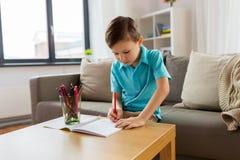 Junge mit Notizbuch- und Bleistiftzeichnung zu Hause Stockfotos