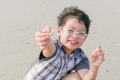 Junge mit Oberteil auf dem Strand Stockfotografie