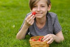 Junge mit organischer Erdbeere stockfotos