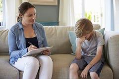 Junge mit Problemen zu Hause sprechend mit Ratgeber Lizenzfreies Stockbild