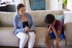 Junge mit Problemen zu Hause sprechend mit Ratgeber Stockfoto