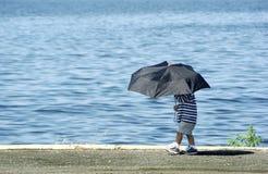 Junge mit Regenschirm Stockfotografie