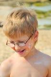 Junge mit Sahne auf Ihrem Gesicht stockbild