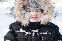 Junge mit Schnee auf ihrem Gesicht lizenzfreie stockfotos