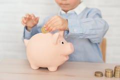 Junge mit Schweinsparschwein Kindheit, Geld, Investition und Konzept der glücklichen Menschen lizenzfreies stockbild