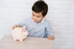 Junge mit Schweinsparschwein Kindheit, Geld, Investition und Konzept der glücklichen Menschen stockfotografie